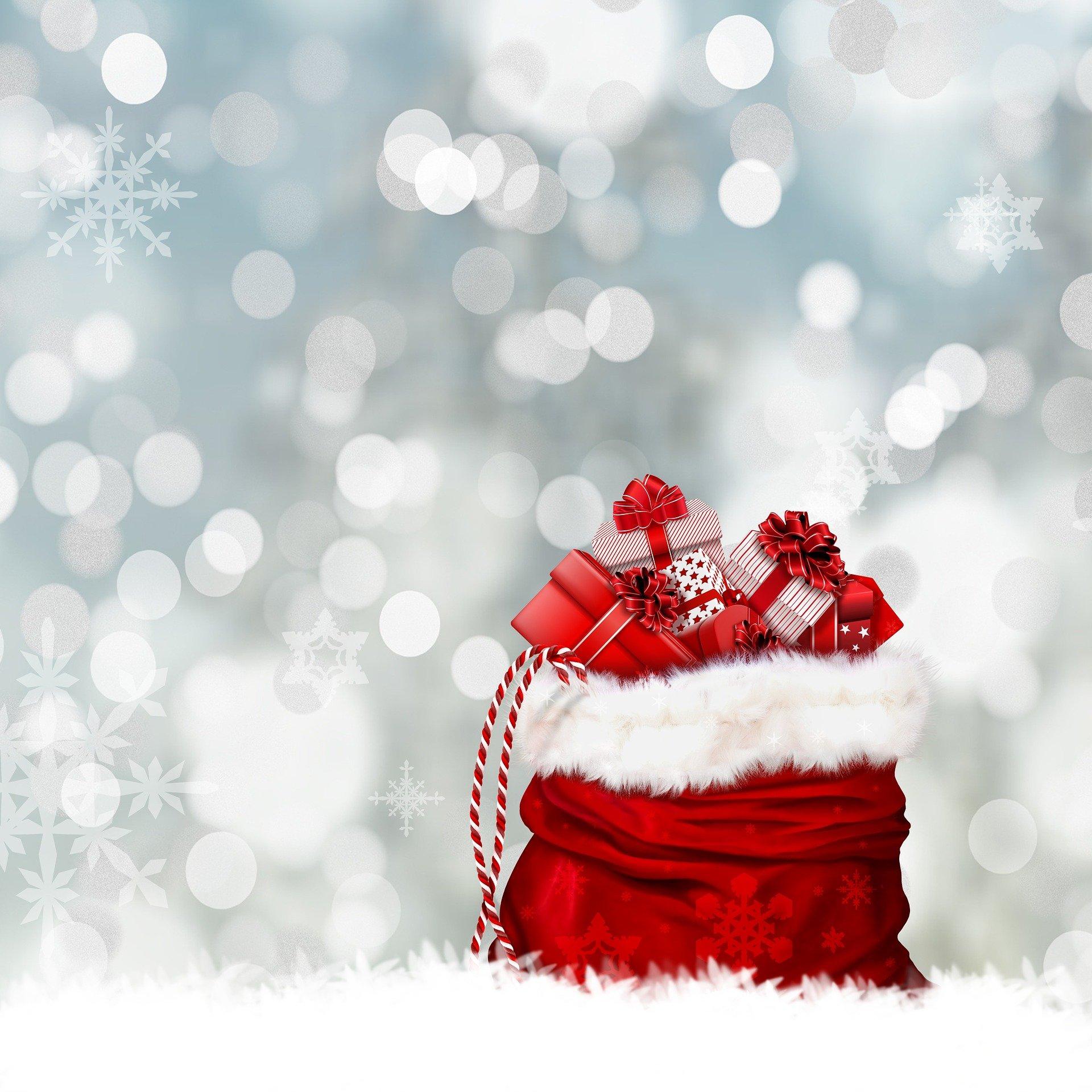 Sac rouge de cadeaux de Noël sur fond de neige
