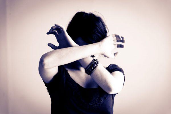 Une femme se protège le visage avec ses avant-bras